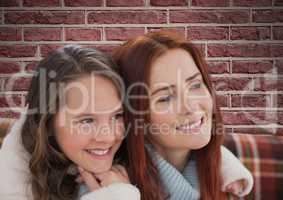 Composite image of mother with her daughter against bricks wall