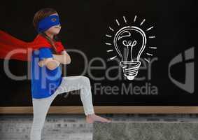 Super Hero kid and blackboard with lightbulb against a black background