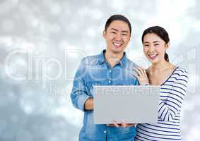 Happy Couple using Laptop against a shining grey background