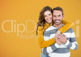 Happy Couple Hug and smilling at camera against a Yellow Background