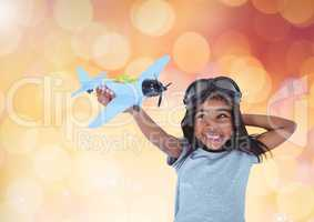 Happy Kid Boy Playing with toy against a shining orange background