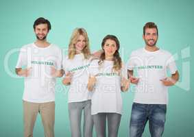 Happy Volunteers Teams pointing at tee shirt against green background