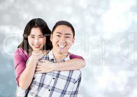 Happy Couple Hug and smilling at camera against a grey Background