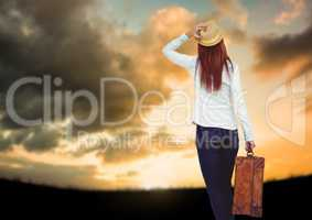 Woman holding Luggage against sky background