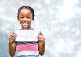 Kid holding a paper smiling against a shining background
