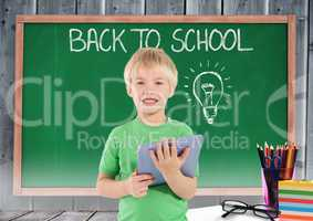 kid and green blackboard with lightbulb against a wood background