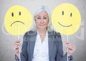 Senior businesswoman holding smileys against grey textured wall