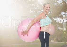 Portrait of pregnant woman holding exercise ball in the park