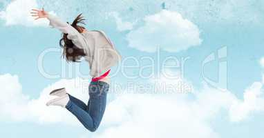 Woman jumping in mid-air against cloudy sky background