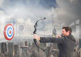 Businessman aiming at the target board against cityscape in background
