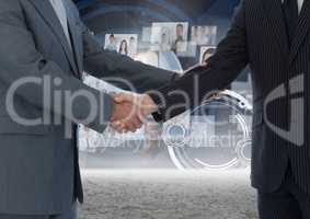 Business professionals shaking hands against technology background