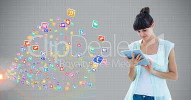 Woman using digital tablet against application icons