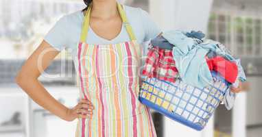 Mid section of woman with apron holding a laundry basket