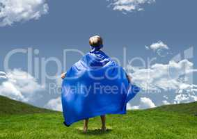 Boy in superhero costume standing on grasslands against sky in background