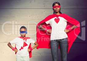 Mother and son in superhero costumes standing with hands on hips