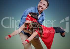 Dad carrying his daughter in superhero costume against green background