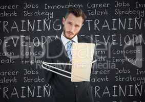 Portrait of businessman tied up with rope and folder against business concept on chalkboard
