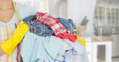 CleanerMid section of woman with apron holding a laundry basket