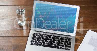 Laptop with document and glass of water on wooden table