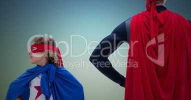 Dad and daughter in superhero costume with their hands on hips standing