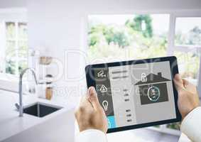 Hands holding digital tablet with home security icons