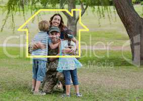 Family hugging each other in the park against house outline in background