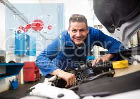 Mechanic working in garage against car mechanics interface in background