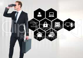 Businessman with briefcase looking through binoculars standing against various applications