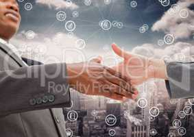 Business professionals shaking hands with handcuff against digital interface in background