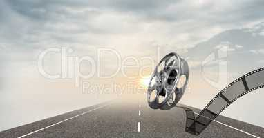 Film reel against road and sky in background