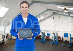 Mechanic holding a digital tablet against workshop in background