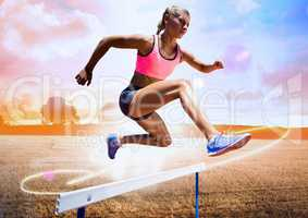 Athlete running over hurdle in field against bright sunlight