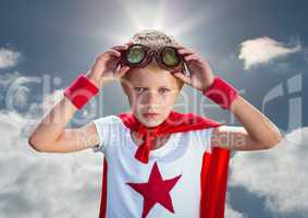 Confident boy wearing superhero costume standing against cloudy sky background