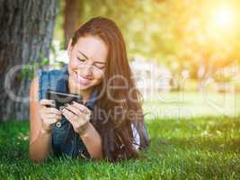 Mixed Race Young Female Texting on Cell Phone Outside In The Gra