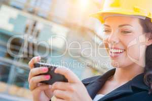 Female Contractor Wearing Hard Hat on Site Texting with Cell Pho
