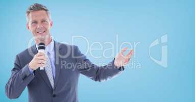 Businessman speaking with microphone against blue background