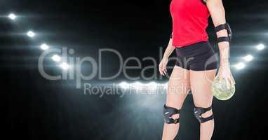 Female athlete holding handball against flood lights in background