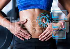 Fit woman showing abdominal muscles and fitness interface in background