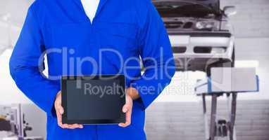 Mechanic holding a digital tablet at workshop