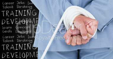 Digital composite image of a businessman with hands tied and training and development concept