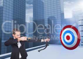 Businessman holding bow and arrow while aiming  at the target board