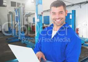 Mechanic using laptop at workshop