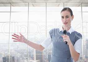 Businesswoman public speaking on microphone against cityscape in background