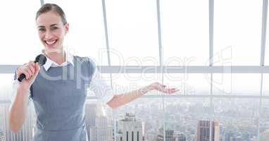 Portrait of businesswoman public speaking on microphone against cityscape
