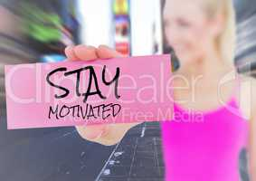 Woman holding placard that reads stay motivated against city