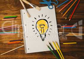 Notebook with light bulb and color pencils on table