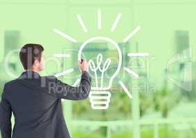 Businessman drawing electric bulb against office window background