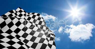 Checkered flag waving against lens flare
