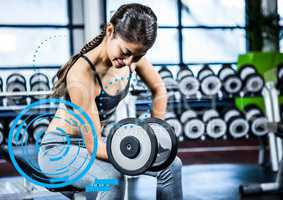 Fit woman performing bicep curl exercise in gym against digital fitness interface
