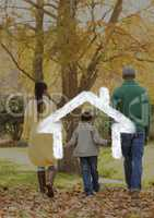 Family walking in the woods against house outline in background